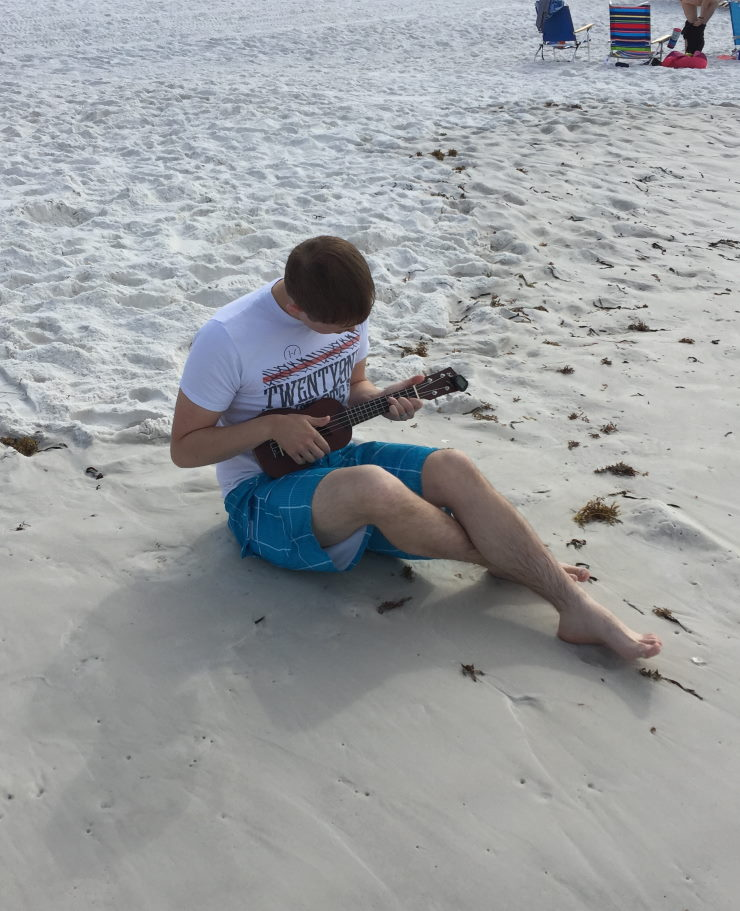 How to be a better father to your teenage son Son playing the ukelele on the beach