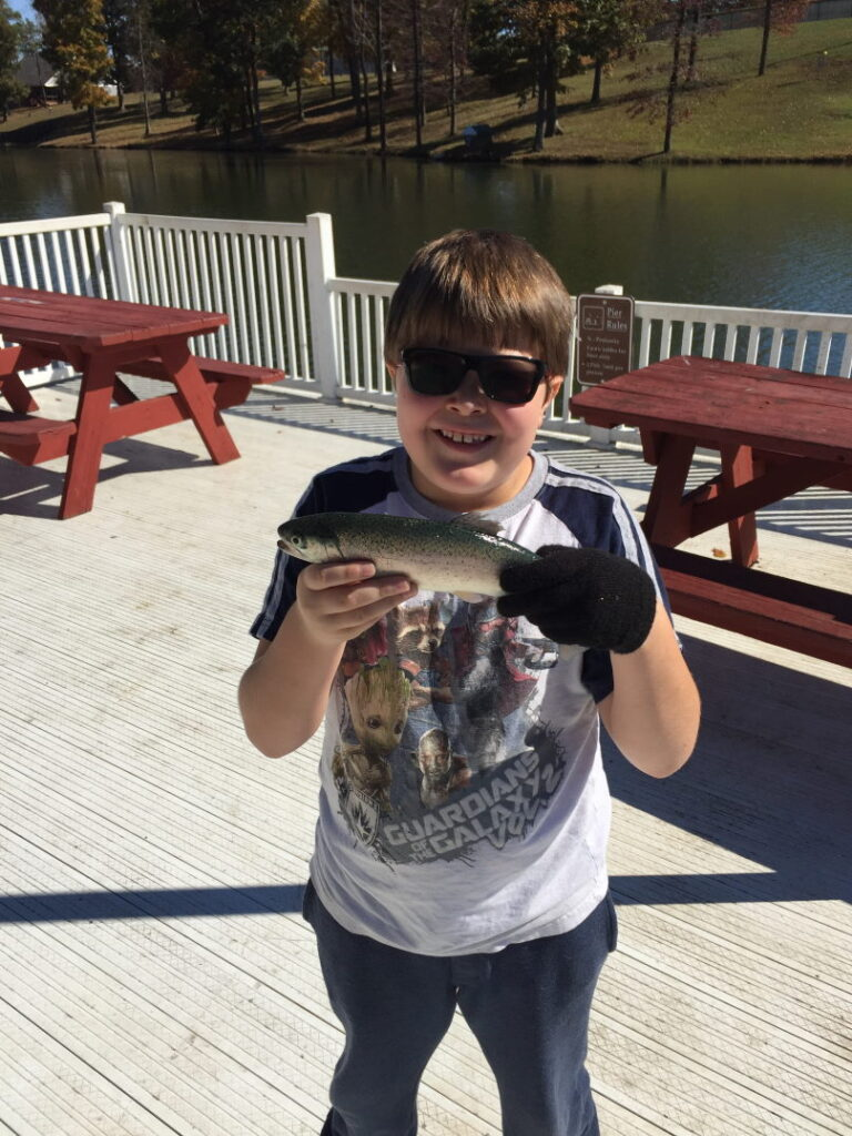 Take a kid fishing  Holding trout and smiling big